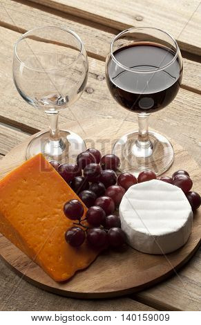 view of a wooden board with wine glass grapes and cheese