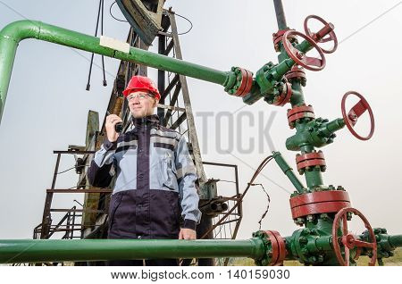 Oilfield worker near wellhead wearing red helmet and work clothes holding the radio. Pump jack background. Oil and gas concept.