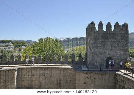 GUIMARAES, PORTUGAL - AUGUST 9, 2015: People at the top of the Castle with views of the city in the background in Guimaraes Portugal.