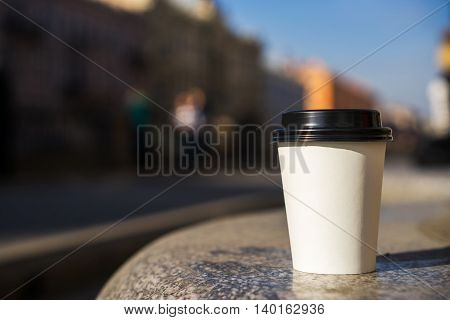 Paper white disposable cup for tea or coffee in the street.