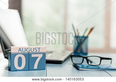 August 7th. Day 7 of month, wooden color calendar on business background. Summer time. Empty space for text.