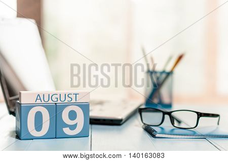 August 9th. Day 9 of month wooden color calendar on business office background. Summer time. Empty space for text.