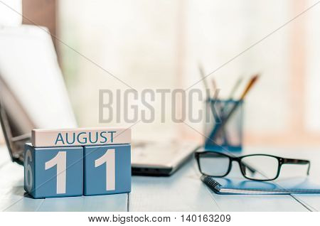 August 11th. Day 11 of month, wooden color calendar on freelance workplace background. Summer time. Empty space for text.