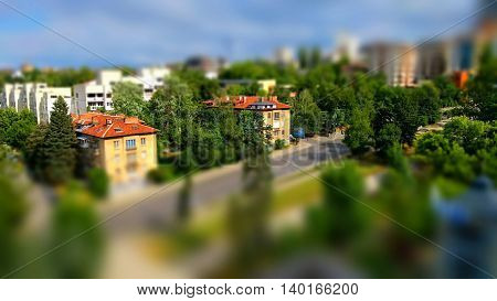 Small toy like miniature tilt-shift effect photo of a residential housing along a boulevard as a green system