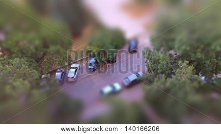Cute toy like miniature tilt-shift effect photo cars in a parking lot revealed between trees