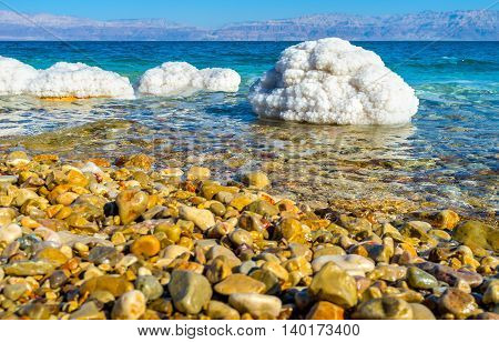 The pebble beach on the Dead Sea with the large covered by salt crystals stones on the background Ein Gedi Israel.