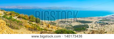 The coast of the Dead Sea is occupied with the palm farms of the local kibbutzes looking so small from the mountain top Ein Gedi Israel.