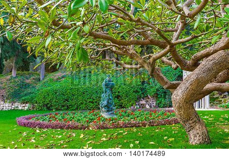 The view on the scenic flower bed with park sculpture with the spreading tree on the foreground Bahai Gardens Haifa Israel.