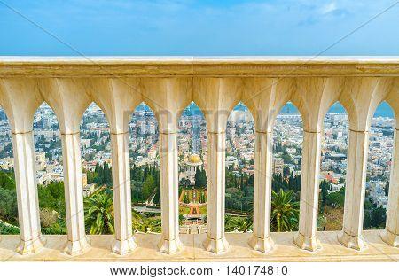 The view on Bahai Gardens and Shrine through the white stone handrail on the top of Carmel Mount Haifa Israel.
