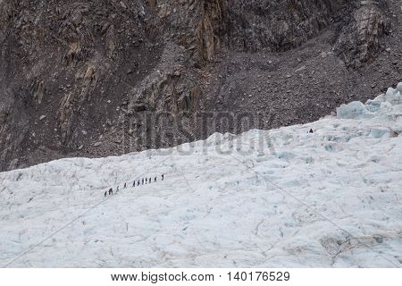 Franz Josef, New Zealand - March 22, 2015: A group of tourists hiking in the distance on Franz Josef Glacier.