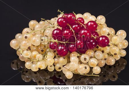 Heap of white currant and redcurrant isolated on black background.