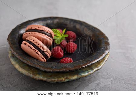 Chocolate french macarons with ganache filling on handmade ceramic plate