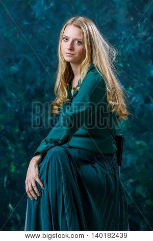 Beautiful Russian blonde girl on a green background in a long green dress