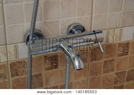 Shiny new bathroom tap. Bathroom faucet. Stainless steel tap.
