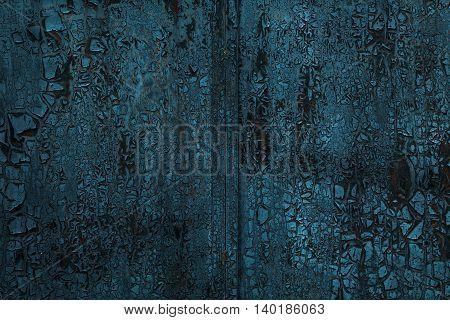 Charred metal surface with peeling paint. Background