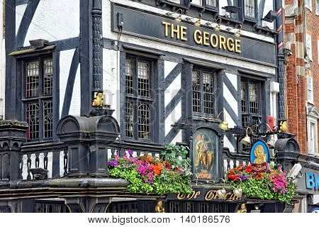 LONDON UK - JULY 1 2014 : The George on Strand. The spectacular architecture in the opposite side of the Royal Courts of Justice It is a traditional English pub.
