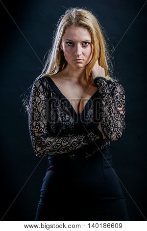 Beautiful Russian blonde girl on a black background in a dark guipure dress