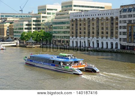LONDON UNITED KINGDOM - JULY 1 2014: A City Cruises tour boat sails on the Thames River near London Bridge Hospital. Thames is the longest river in England with 346 km (215 miles) long.