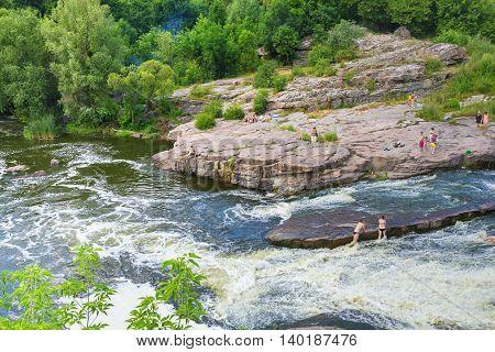 BUKY CHERKASY REGION UKRAINE - JULY 2 2016: People bathing in the river of Buky canyon in Cherkasy region Ukraine