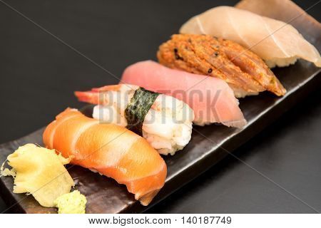 close up of sashimi sushi set on stone plate