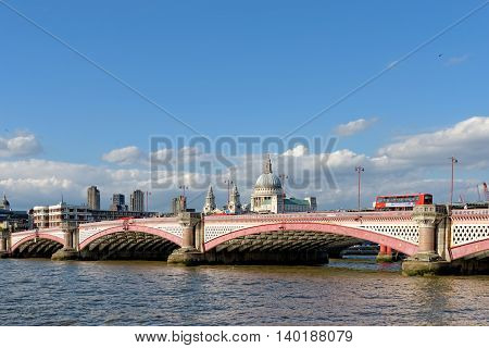 LONDON UK - JULY 1 2014: A view of Blackfriars bridge - a road and foot traffic bridge over the river Thames against a background of St Paul Cathedral and the residential towers of Barbican.