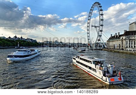 LONDON UK - JULY 1 2014: View of Thames river with cruise tour boats near the giant Ferris wheel nicknamed London Eye.Thames is the longest river in England with the length of 346 km.