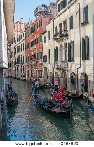 VENICE ITALY - JULY 1 2016: Gondoliers navigate gondolas through a canal in Venice Italy.