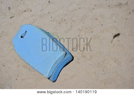 Blue Boogie Board Left on Sandy Beach
