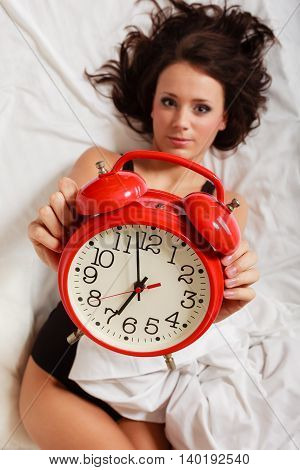 Sexy lazy girl in black body lying with red alarm clock on the bed. Young attractive woman relaxing lazing in her bedroom at the morning.