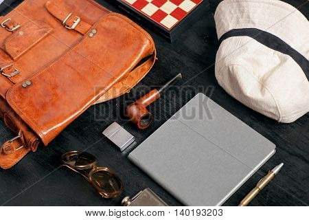Selective focus on different objects and equipment for travel and holiday of a man - sunglasses, notebook, pen, leather bag, white hat, smoking pipe, chessboard