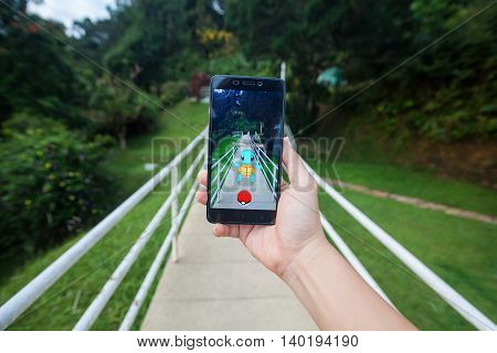 California, United States - July 23, 2016: Hand holding a cellphone to play Pokemon Go with blur garden background
