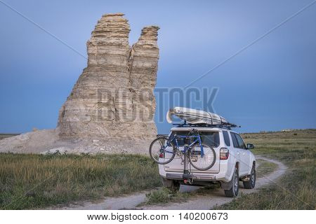 CASTLE ROCK, KS , USA - JULY 25 2016: Family driving Toyota 4Runner SUV (2016 Trail edition) on summer vacations carrying  a kayak and bike in Kansas back country.