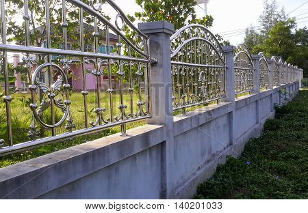 side lit concrete wall with arched decorative scrolled metal railing on top, attached to concrete posts, stretching away from camera to the right, pink two-story house seen through the bars on the left, near Songkhla, Thailand