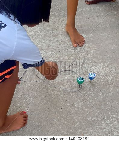 barefoot Thai girl with painted toenails, bending down to capture a spinning, painted homemade top with a loop of string, on a paved playground, bare toes seen nearby, Songkhla, Thailand