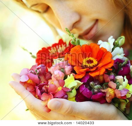 Young woman with flowers over natural background