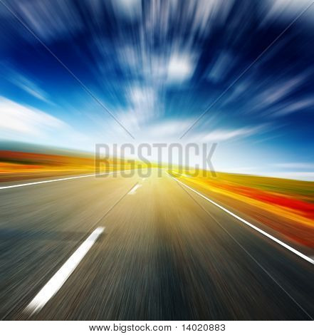 Blurred asphalt road and blue motion blurred sky with clouds and light spot