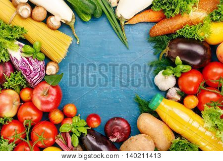 Frame of colorful fruits vegetables pasta and orange juice on blue surface. Frame of colorful fruits and vegetables background top view.