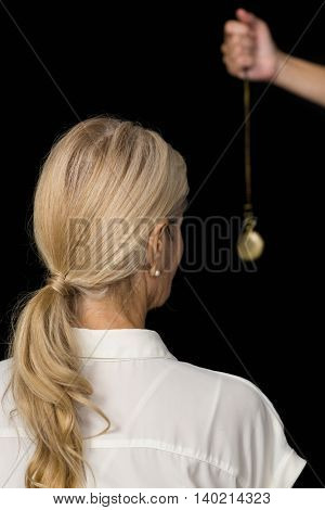 Cropped hand of hypnotherapist holding pendulum by senior woman against black background