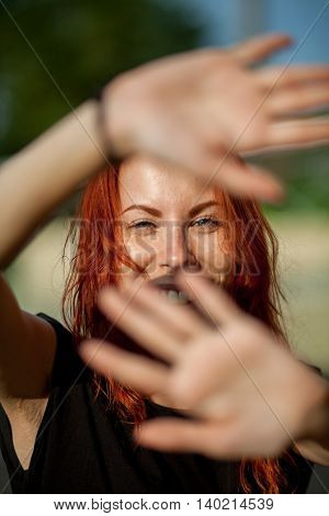 beautiful red-haired girl closes hands from the sun