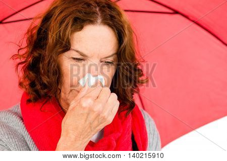 Close-up of mature woman suffering from cold while holding umbrella