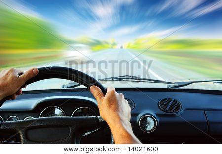 Handen op het stuur van een auto rijden op een wazig asfaltweg