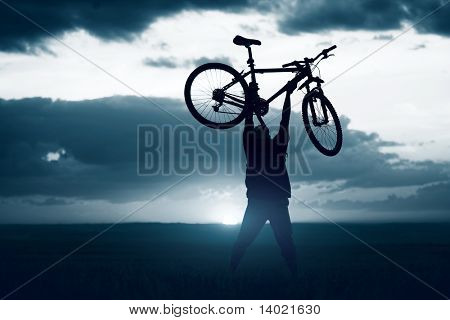 Man with bicycle lifted above him
