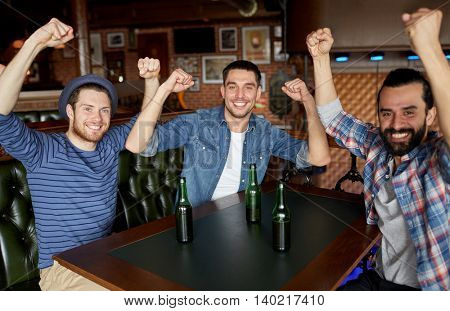 people, leisure, friendship and bachelor party concept - happy male friends drinking bottled beer and having fun at bar or pub