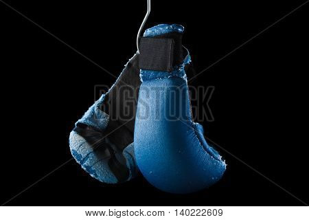 Old boxing or karate gloves hang on nail black background. Retirement concept