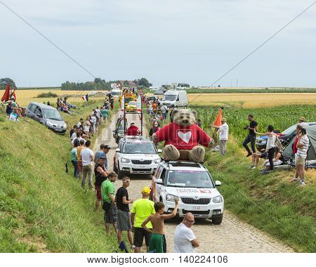 QuievyFrance - July 07 2015: The association Cardiac Surgery - Children of the World Caravan during the passing of the Publicity Caravan on a cobblestoned road in the stage 4 of Le Tour de France on July 7 2015 in Quievy France. The association Cardiac Su
