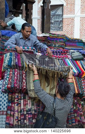 Kathmandu, Nepal - October 19, 2014: A seller showing scarfs to a customer on the market in Kathmandu, Nepal