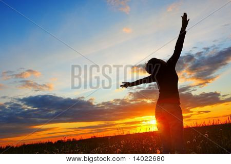 Young woman with raised hands standing on meadow with herbs and looking to a sky