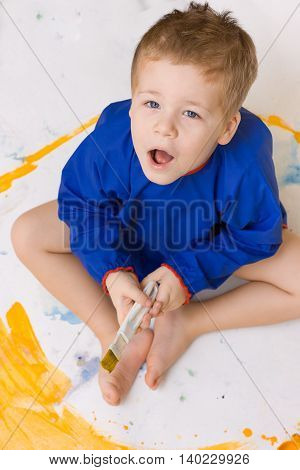Portrait of a cute liitle kid boy sitting on the floor and drawing yellow sun. Young adorable child drawing. Small painter. Artist and bright colors. Creative activities with children indoors. Fun