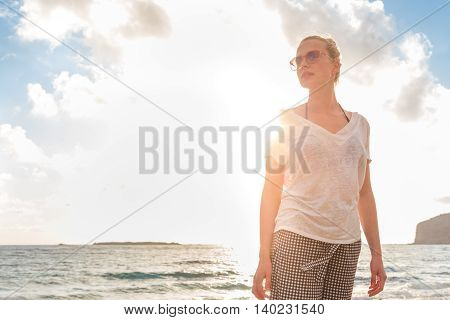Relaxed woman enjoying sun, freedom and life an a beautiful sandy beach. Young lady feeling free, relaxed and happy. Vacations, freedom, happiness, enjoyment and well being.