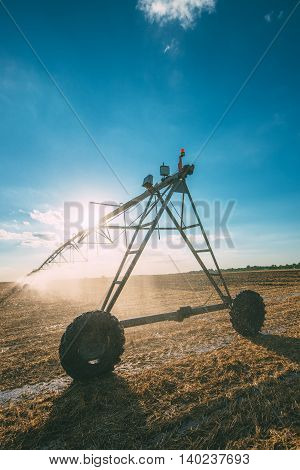 Automated agricultural center pivot irrigation system with drop sprinklers in harvested wheat stubble field in late summer afternoon retro toned